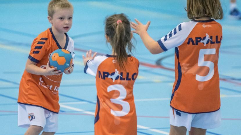 Drie jonge handballers van handbalvereniging Apollo met een handbal