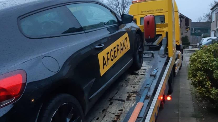Een auto met sticker 'afgepakt' achter op een takelwagen