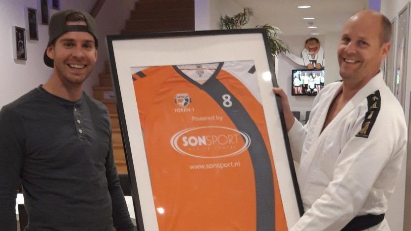 Arjen Brand van Sonsport krijgt het shirt van handbalvereniging Apollo overhandigd