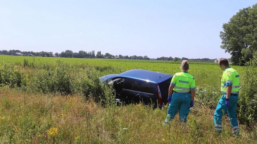 Twee hulpverleners kijken naar een auto die in de sloot langs de A50 is gereden