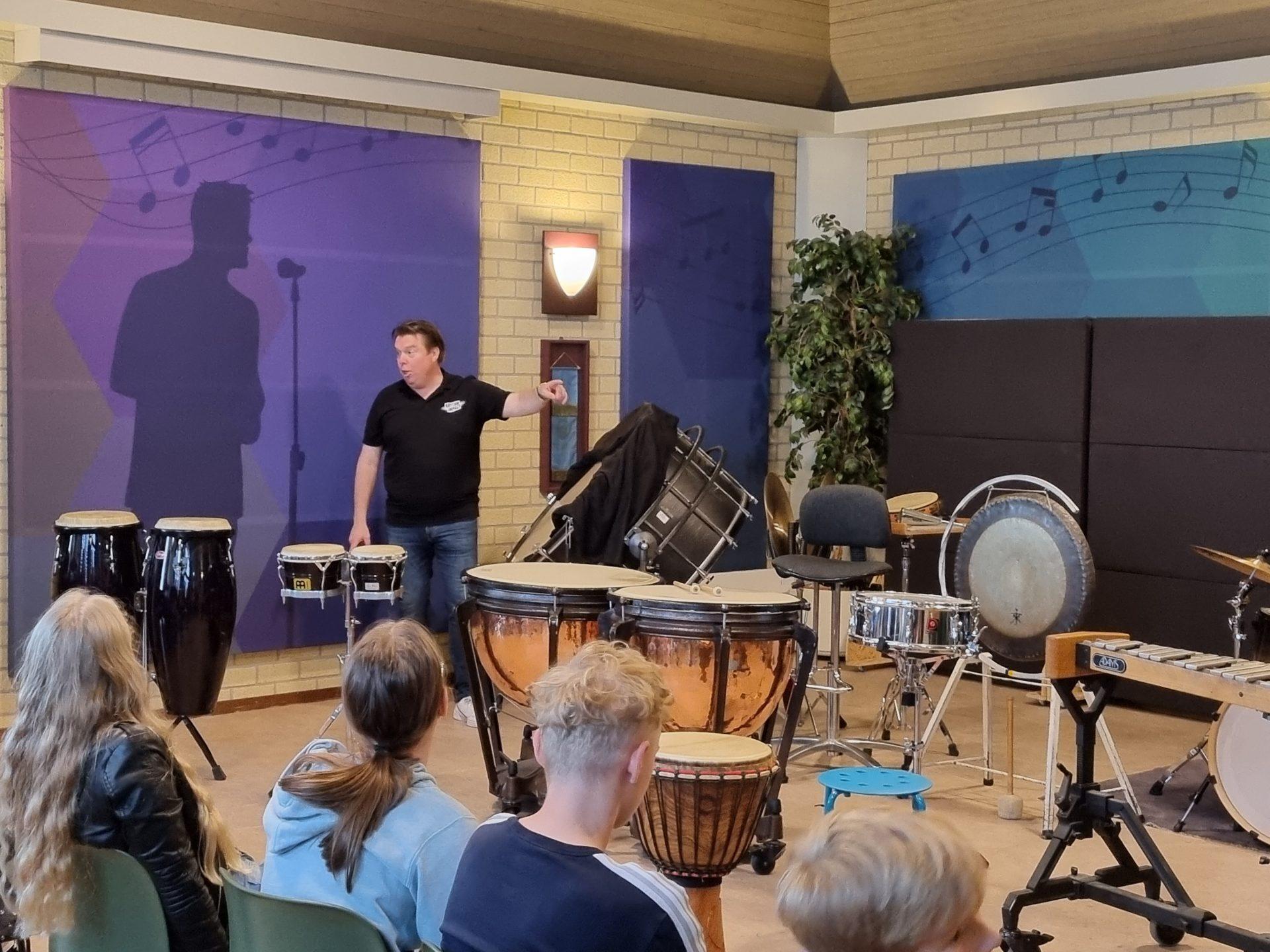 Docent van Rhythm Impact speelt de trom voor kinderen van basisschool de Stokland