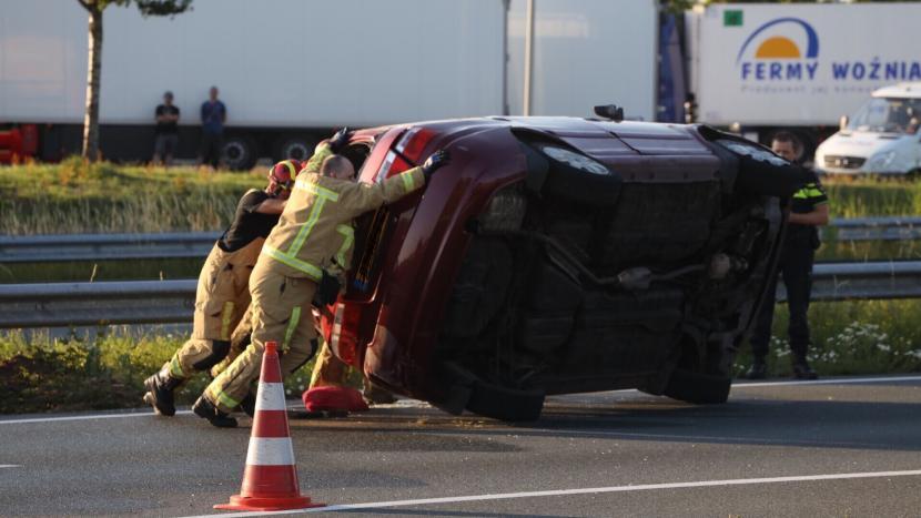 De op de A50 over de kop geslagen rode auto wordt door de brandweer rechtop geduwd