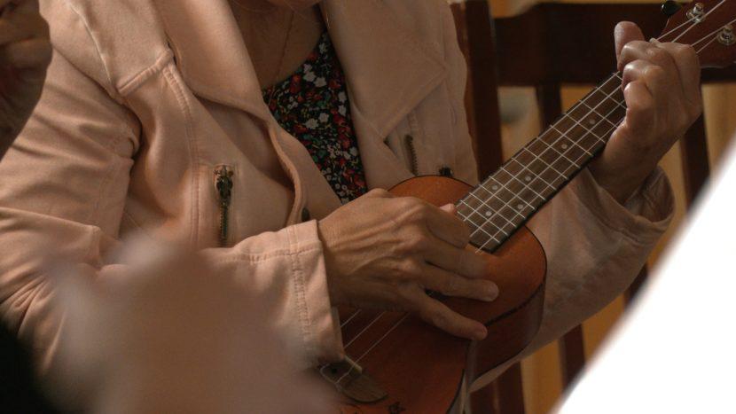 Een ukelele die bespeeld wordt bij Music Dock