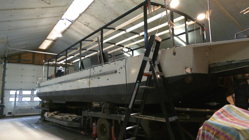 Rondvaartboot dew Waterengel in de loods in Sint-Michielsgestel waar volop aan gewerkt wordt
