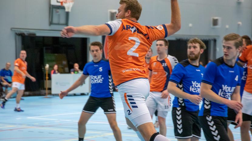 Speler van de heren 1 van Handbalvereniging Apollo springt om de bal te gooien