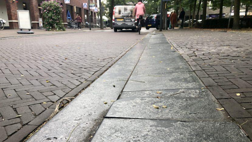 De loslatende coating op de natuurstenen trottoirbanden in het centrum