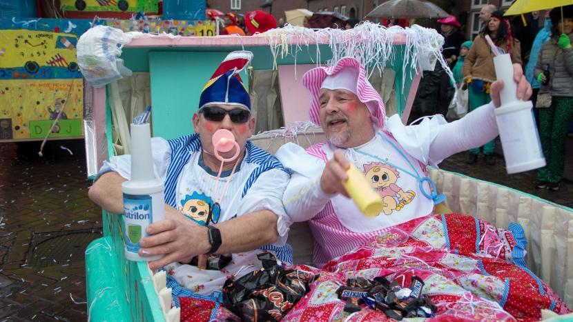 Twee mannen verkleed als baby tijdens de optocht met carnaval in Krutjesgat