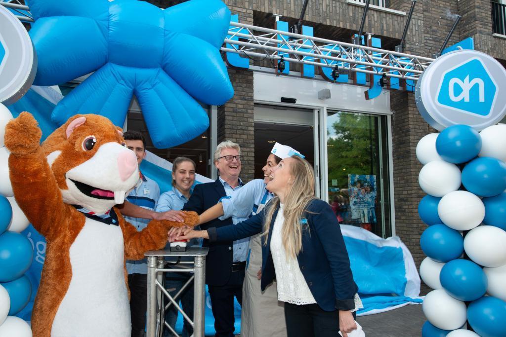 Medewerkers van Albert Heijn Son drukken op de knop om de verbouwde winkel te openen