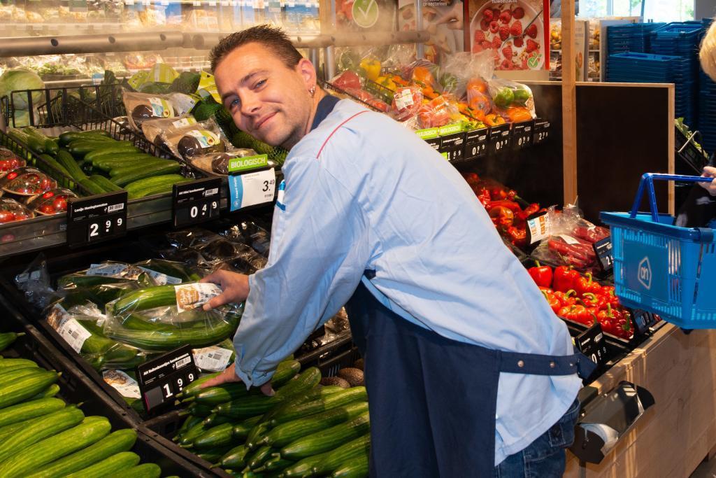 Een medewerker van de versafdeling van Albert Heijn die groente aanvult