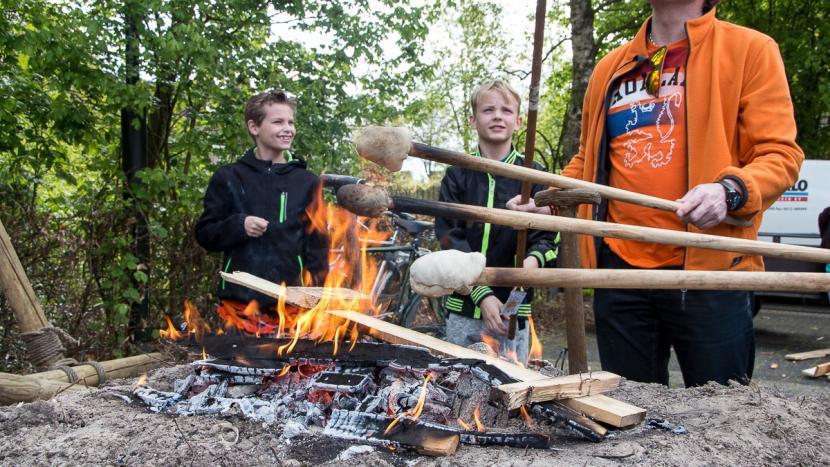 Brood bakken op een stok boven een vuurtje op koningsdag