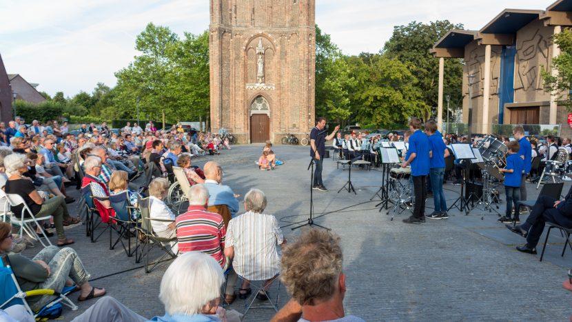 Publiek luistert naar het klapstoelenconcert op het Kerkplein
