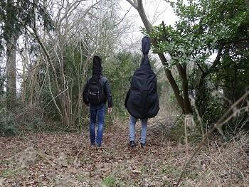 Twee muzikanten met instrumenten op hun rug die een bos in lopen