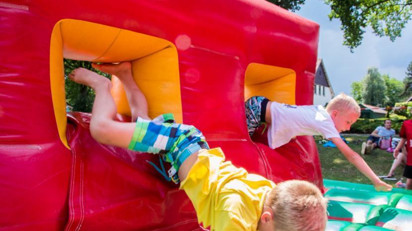 Twee kinderen springen door een opblaasbare hindernisbaan tijdens het zomerspektakel