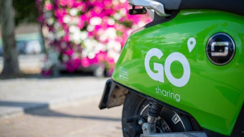 De achterkant van een groene elektrische Go Sharing E-scooter