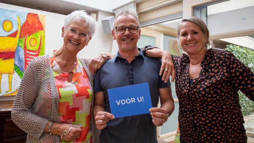 Marianne van der Putte, Stephen Philippi en Helga Helders met de blauwe ansichtkaart met Voor U