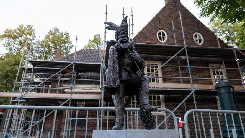 Het beeld van prins carnaval met het Raadhuis in de steigers