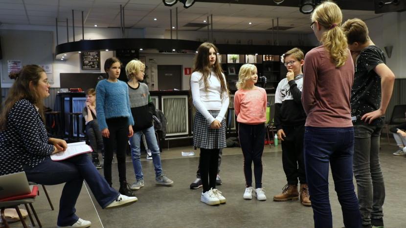 Acteurs van toneelgroep Oase overleggen met docente Femke de Jager
