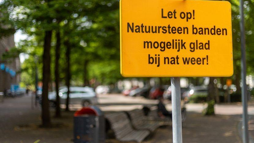 Waarschuwingsbord aan het 17 Septemberplein met de tekst 'Let op: natuursteen banden mogelijk glad bij nat weer'