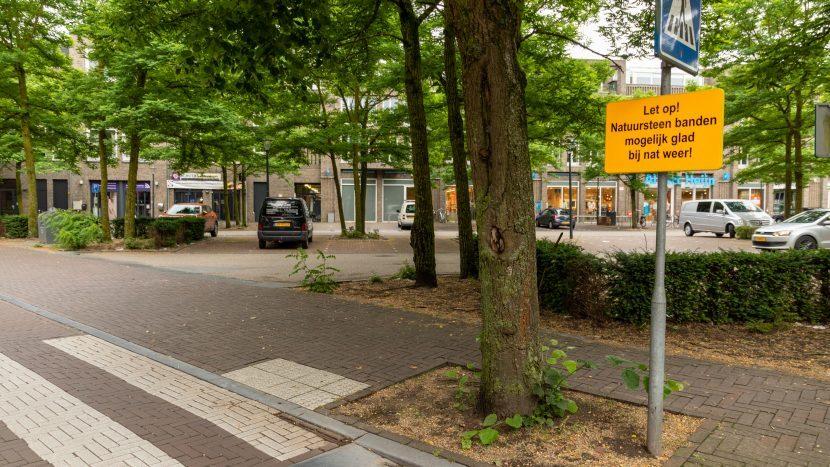 Het 17 septemberplein met waarschuwingsbord met de tekst 'Let op: natuursteen banden mogelijk glad bij nat weer'