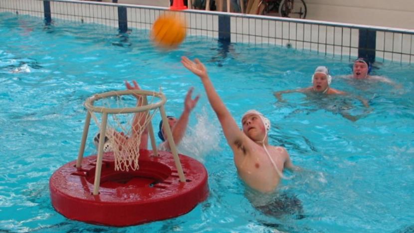 Een doelpoging in het zwembad tijdens waterbasketbal