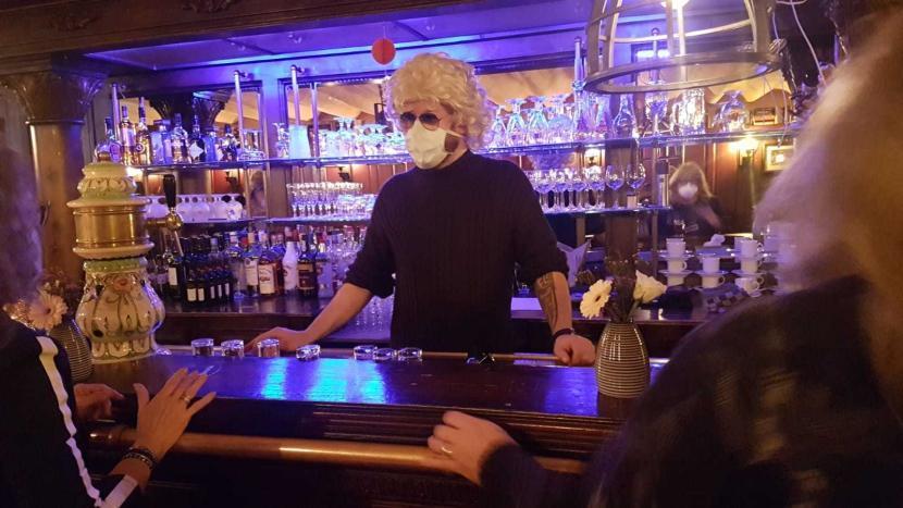 Een barman met mondkapje achter de bar