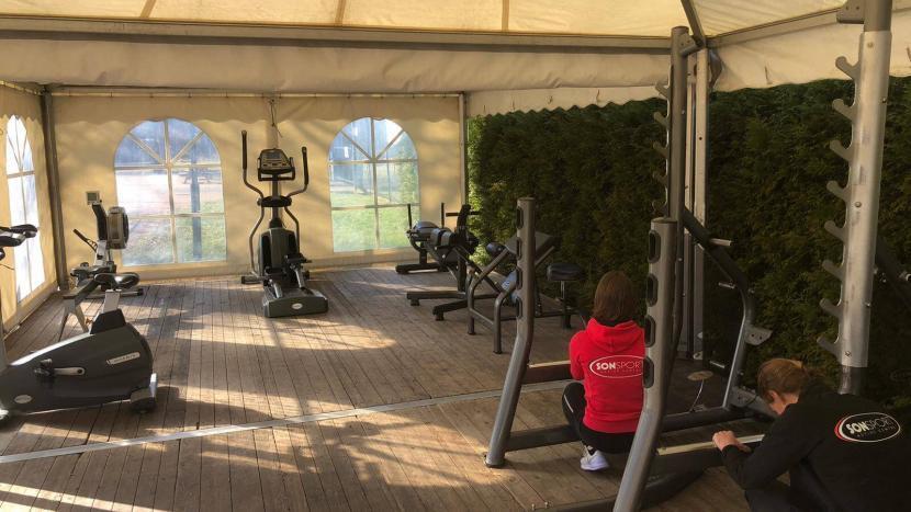 Fitness apparatuur wordt gereed gemaakt in de tent door het personeel van Sonsport