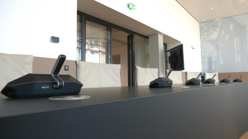 De microfoon/microfoons op de tafel in de raadzaal van de gemeenteraad