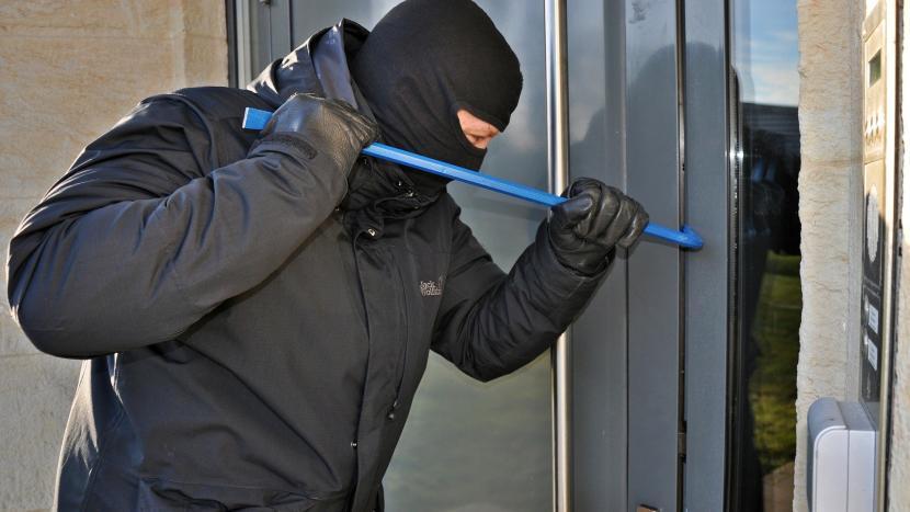 Inbreker die met een koevoet een deur forceert