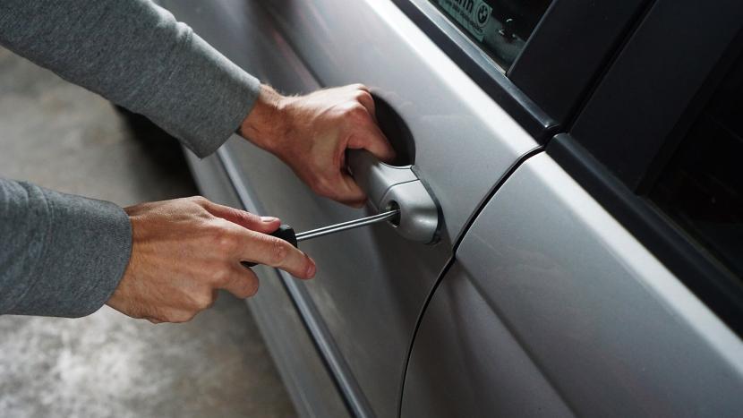 Dief die een autoslot forceert met een schroevendraaier