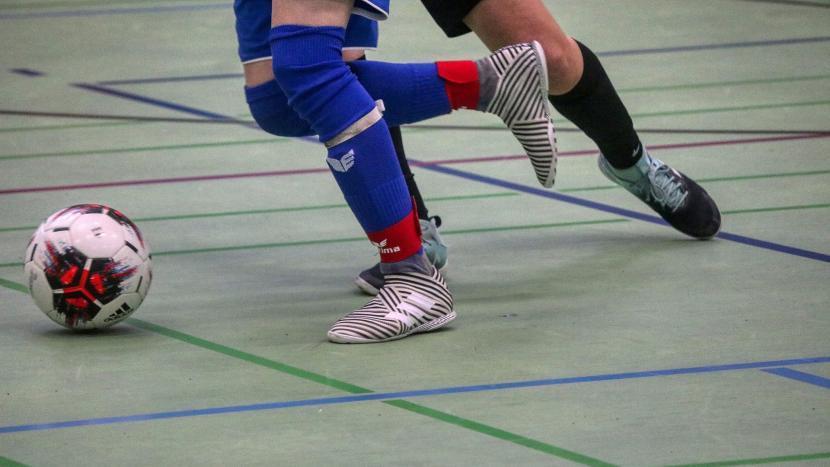 Twee paar benen die achter een bal aanrennen tijdens het zaalvoetbal