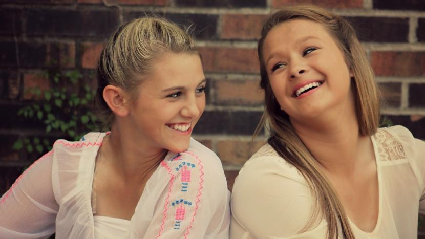 Twee meiden die gezellig met elkaar lachen