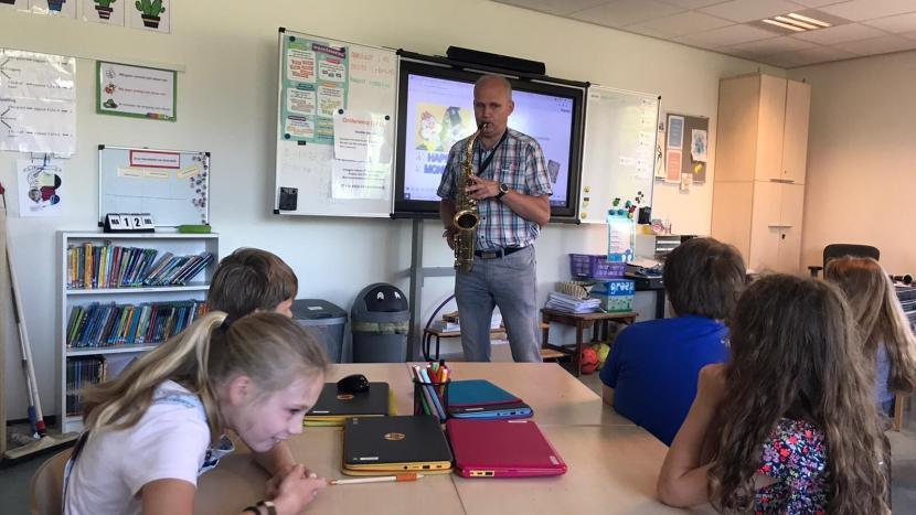 Docent van 040Muziek speelt de saxofoon voor kinderen van basisschool de Stokland