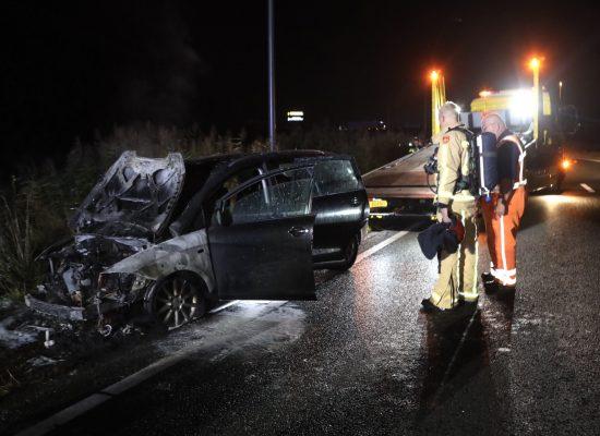 De uitgebrande auto op de A50 met twee brandweerlieden
