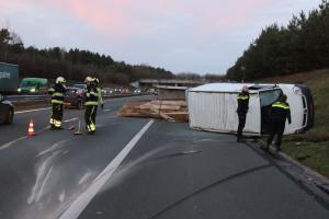 Asfalt beschadigd na kantelen bestelbus met aanhanger op A50