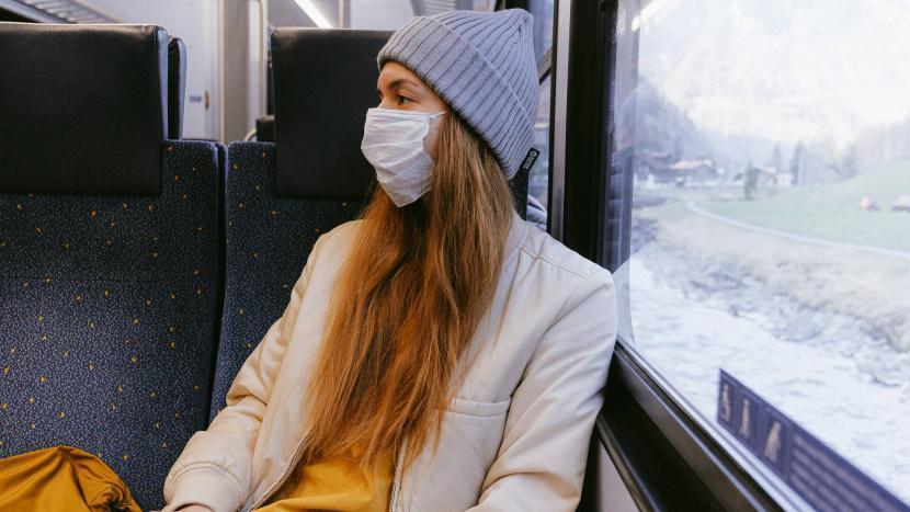 Meisje met mondkapje in de trein