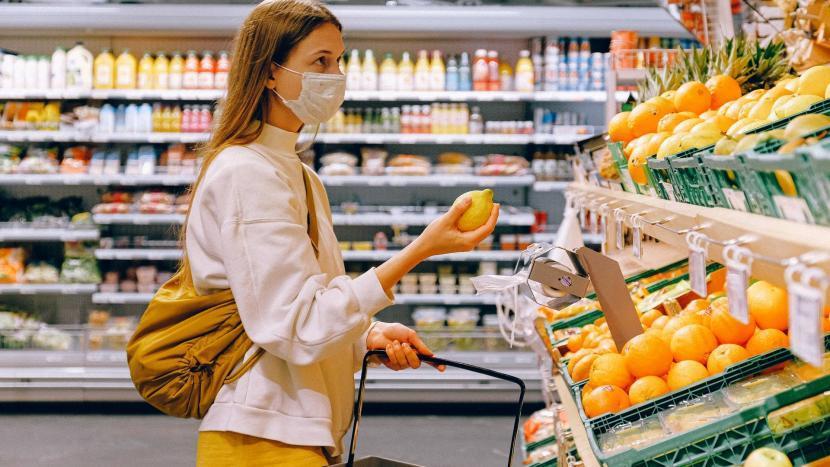 Vrouw met mondkapje bekijkt het fruit in een supermarkt