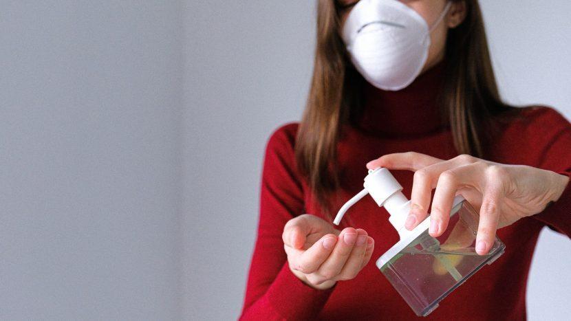 Vrouw met mondkapje doet desinfecterende gel op haar hand