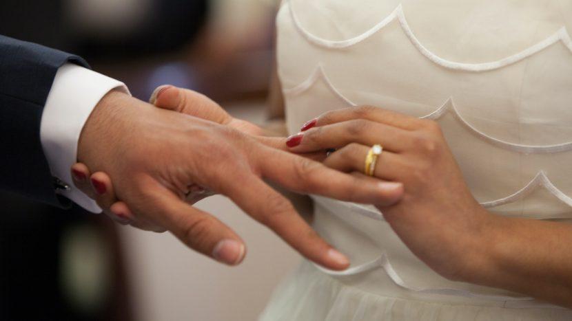 Bruid schuift trouwring op de vinger van de bruidegom