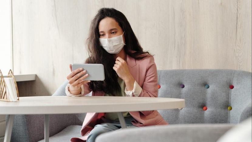 Een vrouw met mondkapje dat aan het videobellen is op haar telefoon