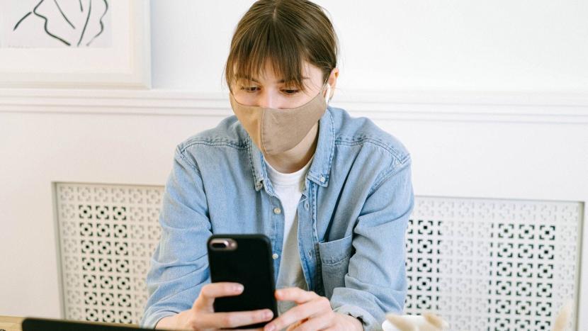 Vrouw met een mondkapje kijkt op haar smartphone