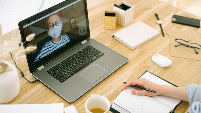 Videobellen op een laptop aan een bureau met iemand die een mondkapje op heeft