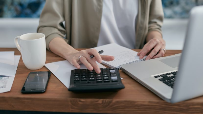 Vrouw werkend achter een laptop met een rekenmachine