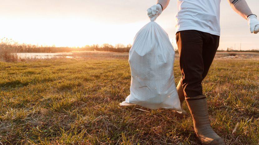 Een vuilniszak gedragen door een man op een veld om de afvalstoffenheffing te illustreren