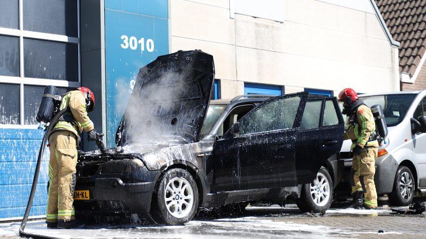 Brandweer die onder de motorkap de auto blust