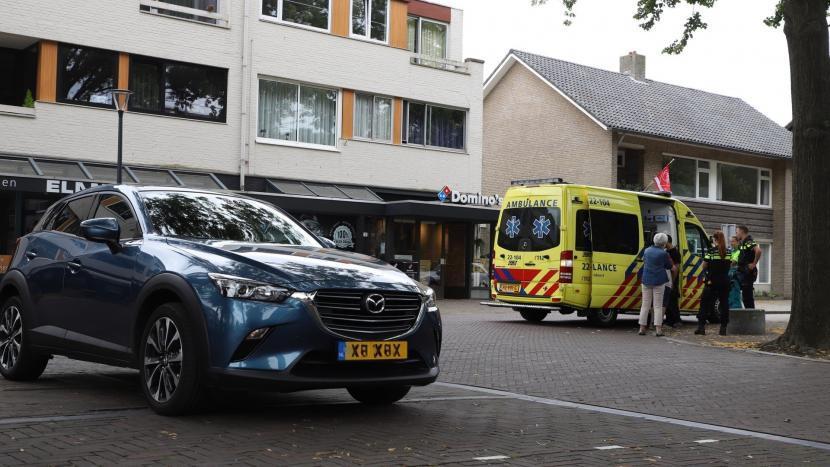 De auto die betrokken is bij het ongeval met een ambulance waar de gewonde verzorgd wordt