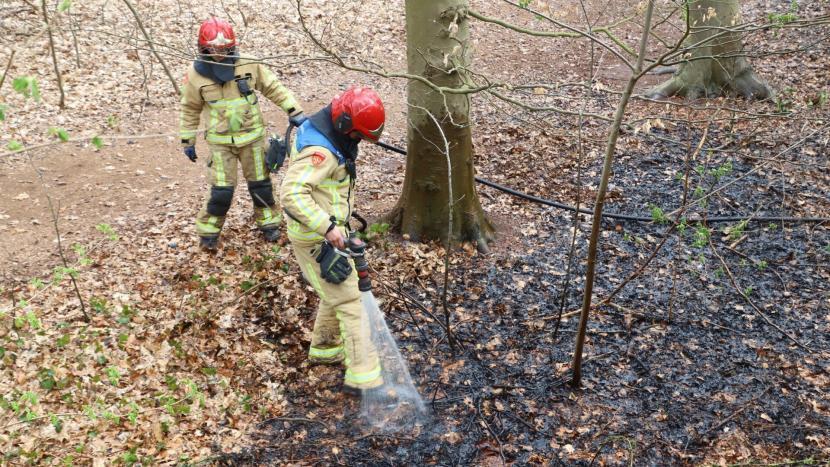 Brandweer blust de bermbrand in de Gentiaanlaan