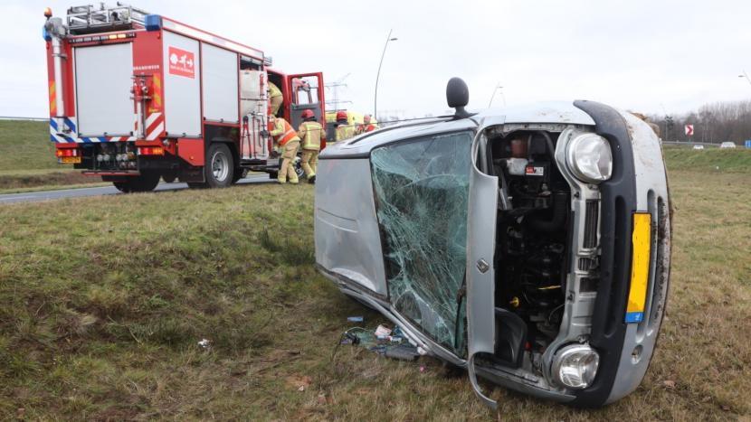 Auto die over de kop is geslagen in het gras langs de A50