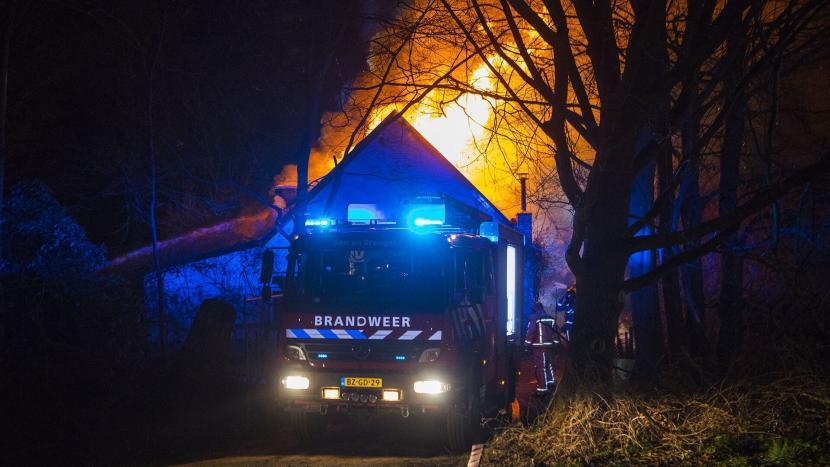 Brand in een woonboerderij met een brandweerwagen op de oprit