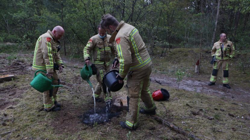 Brand wordt door de brandweer geblust me gieters en een emmer water