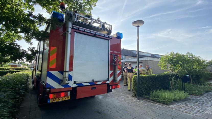 Brandweerlieden overleggen bij de brandweerwagen in de Neptunusstraat
